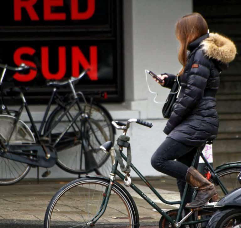 Frau mit Smartphone auf Fahrrad