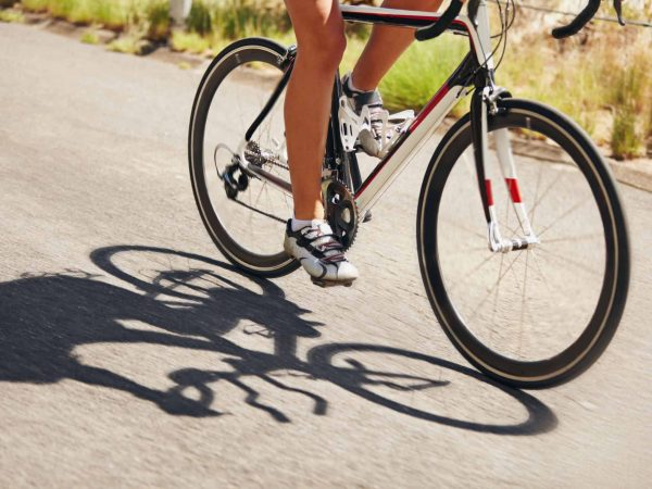Low section image of woman riding bicycle on country road. Cropped image of female athlete cycling. Action shot of a racing cyclist.