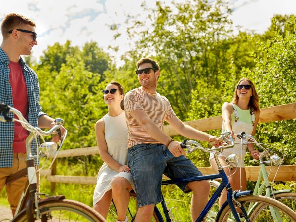 people, leisure and lifestyle concept – happy young friends riding fixed gear bicycles on country road in summer